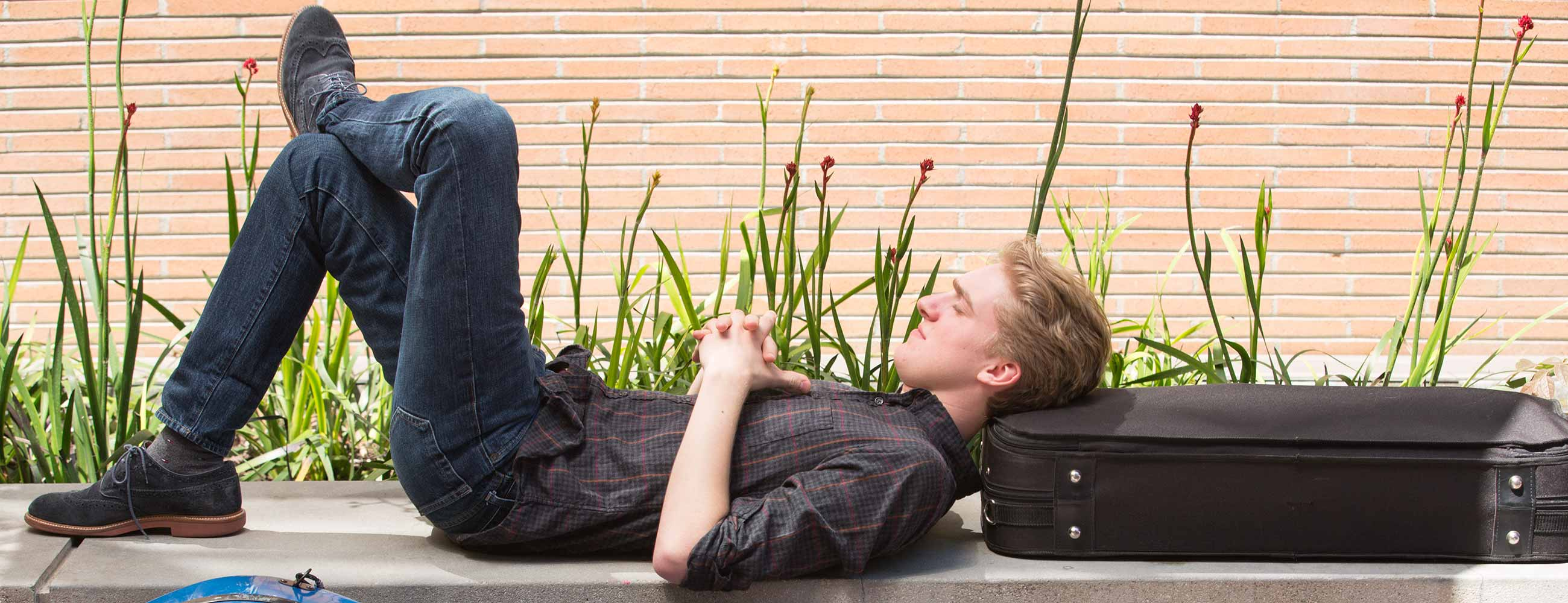 student resting on instrument case