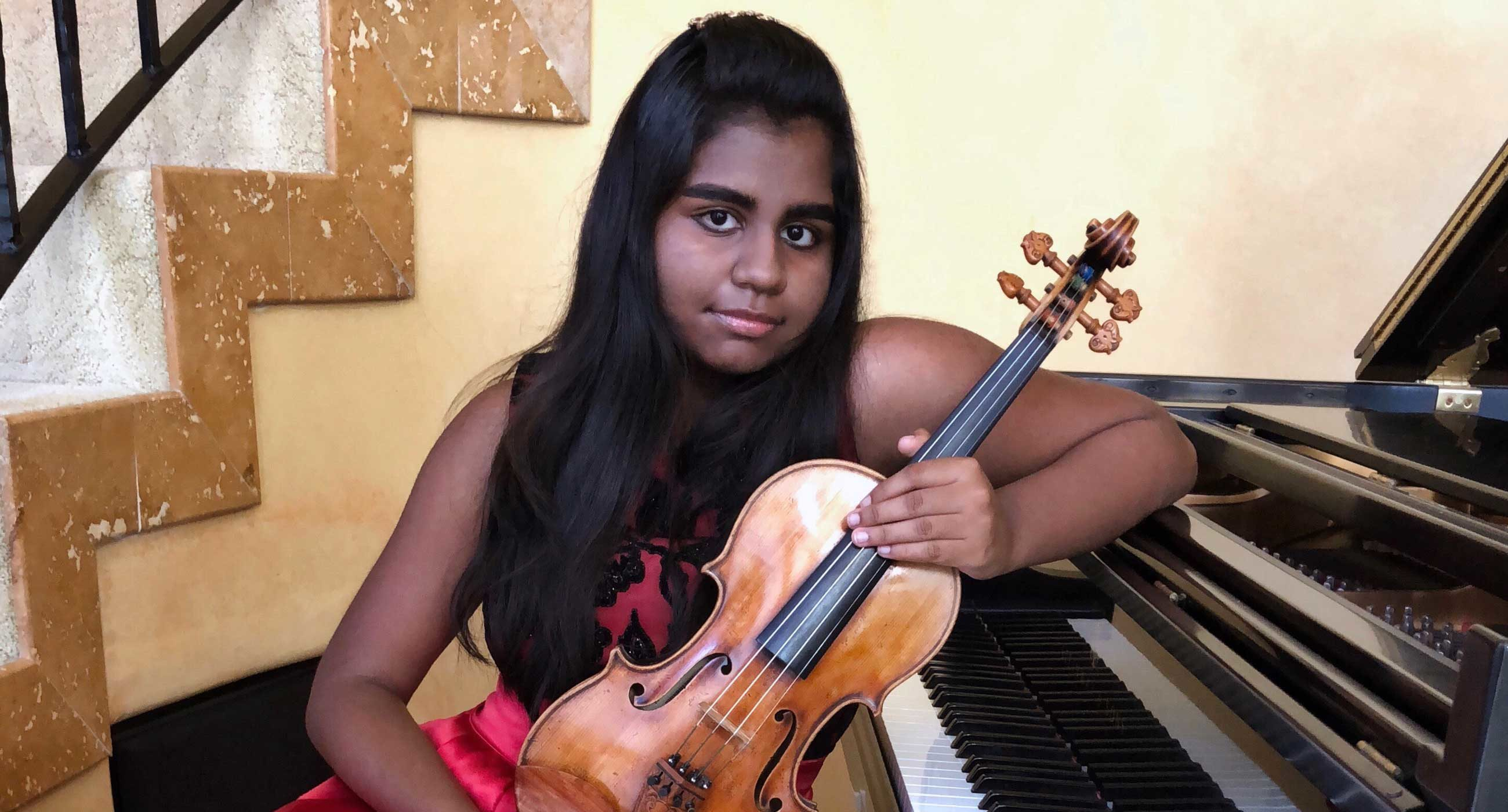 Apsara Kasiraman sitting by a piano holding a violin