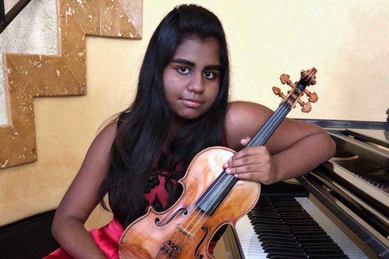 Apsara Kasiraman sitting by a piano holding a violin