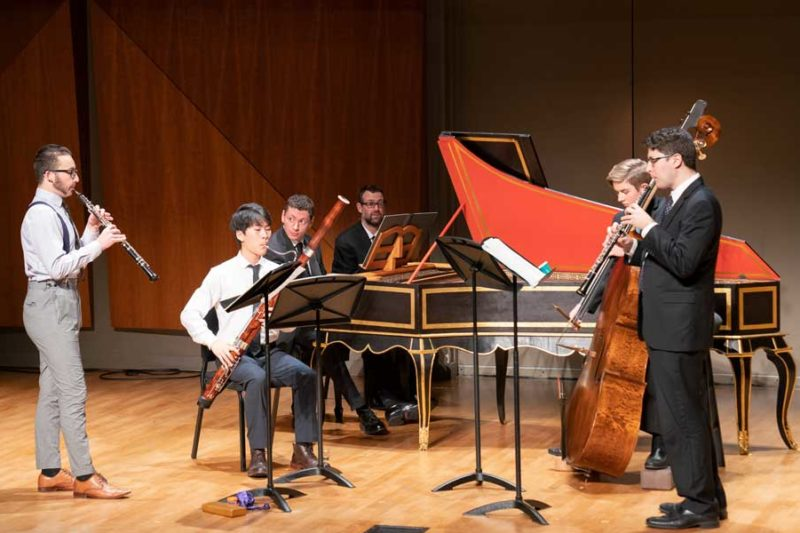 Oboe, harpsichord, bassoon, double bass players on stage performing