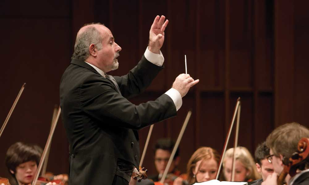A conductor in front of string players conducting.