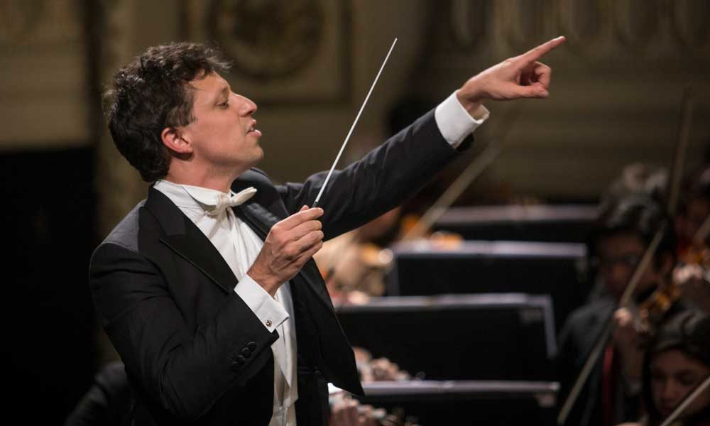 Paolo Bortolamelli holding a conducting baton in one hand and pointing with the other.