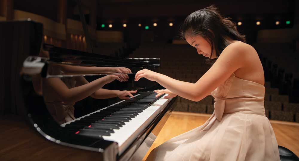 A person in a dress playing piano.