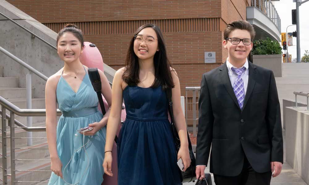 Three high school age students walking down steps. One is in a suit and two are in dresses.