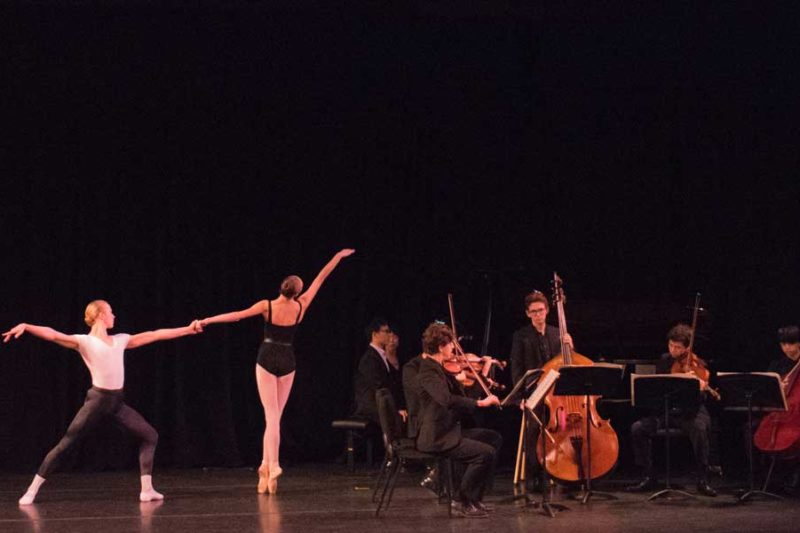 Two ballet dancers dancing together in front of an ensemble with a bass, piano, viola, cello, and two violins.