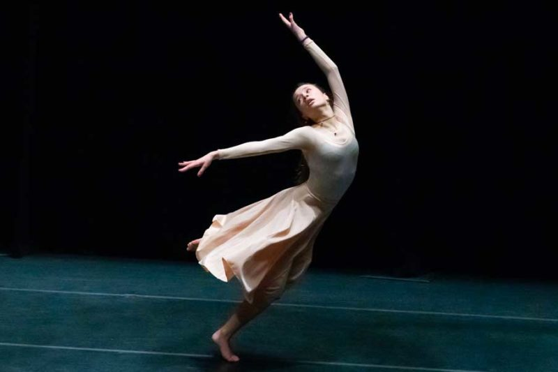 A ballet dancer reaching upwards and moving forwards.