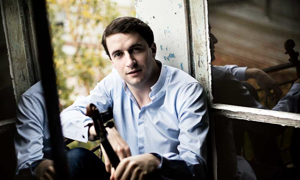 Noah Bendix-Balgley holding a violin and sitting in the window of an old home.
