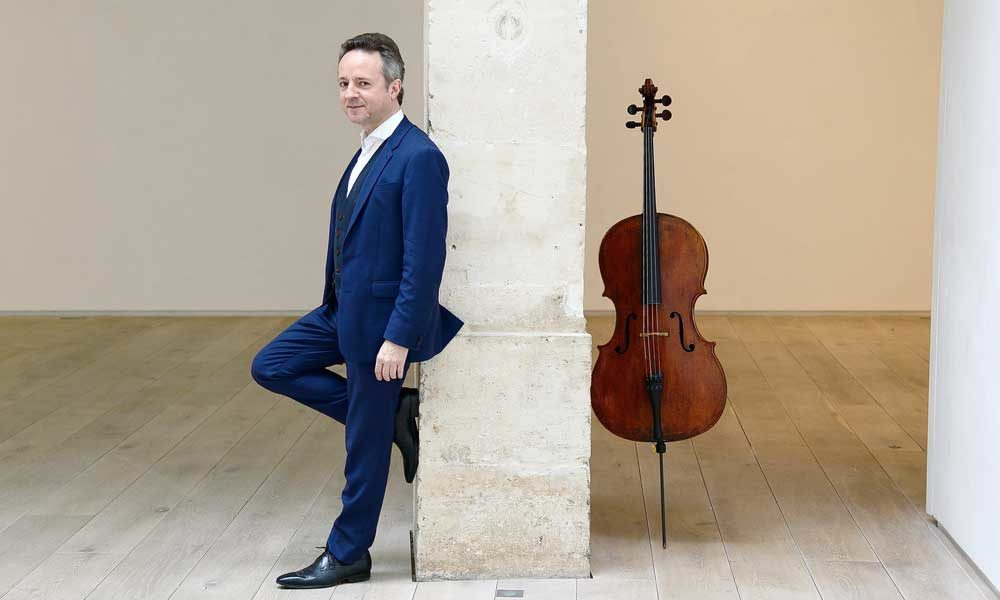 Marc Coppey leaning against a pillar in a full suit. His cello is leaning against the other side of the pillar.