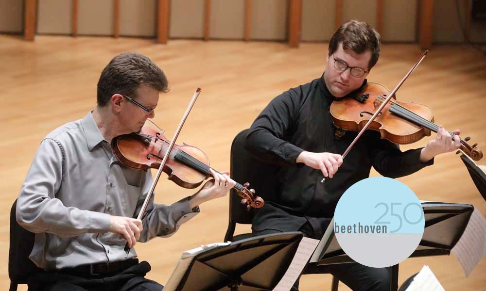 Two faculty members playing violin and viola, respectively.