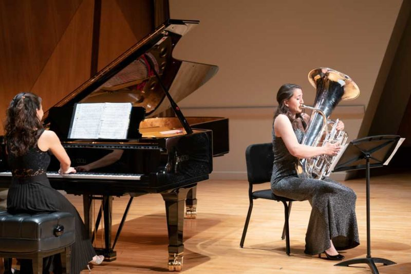 A tuba player in a dress performing with a piano accompanist.
