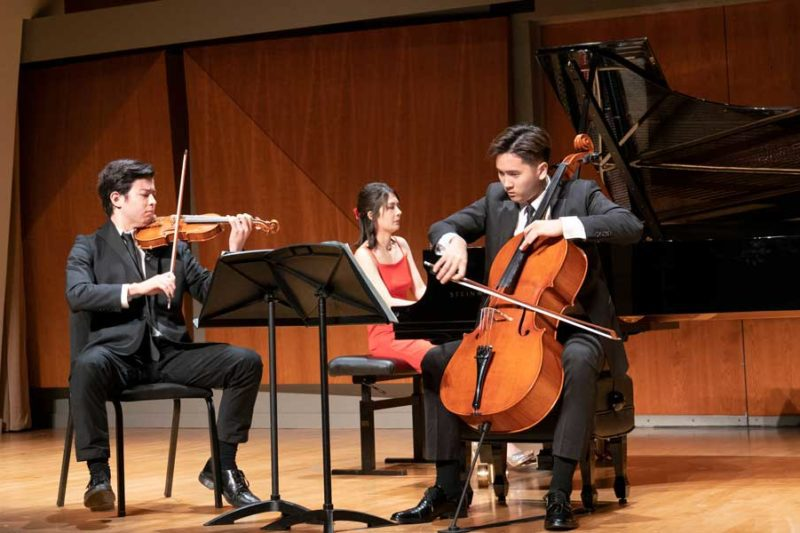 A cellist and a violinist playing in front of a piano accompanist.
