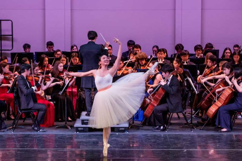 A ballet dancer in a knee-length tulle dress on pointe in front of a string orchestra.