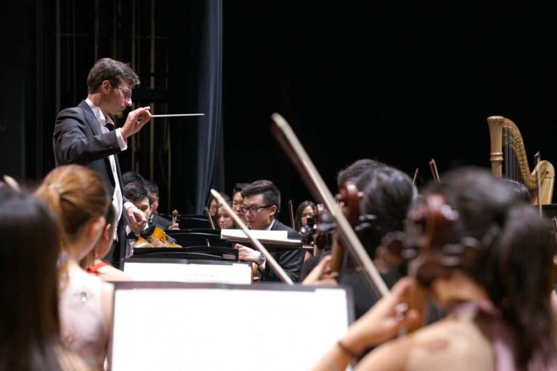 A conductor in front of an orchestra. There is a harp visible in the background.