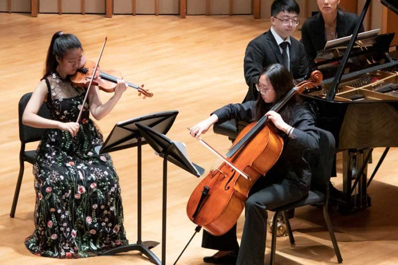 A violinist and a cellist performing with a piano accompanist.