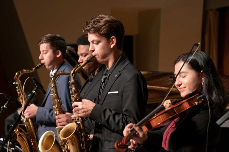 Colburn Jazz Workshop students performing. Three saxophonists and one violinist.