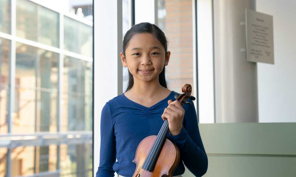 An elementary school aged student holding a violin and smiling in front of a window.