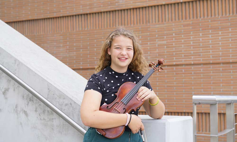 A young student holding a viola and leaning on a railing, smiling.
