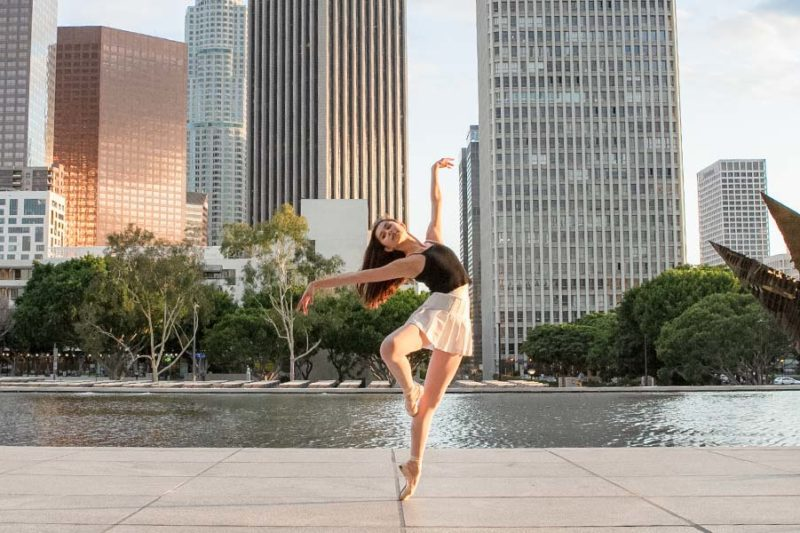 A ballet dancer in a skirt on pointe in front of a body of water in a city.