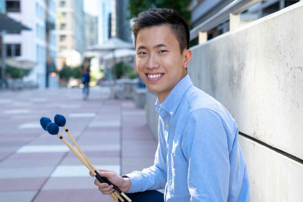 Tsz-Ho Samuel Chan holding mallets outside.