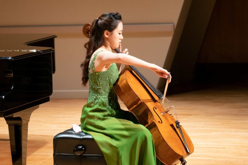 Sanga Yang in a dress playing cello in front of a piano.