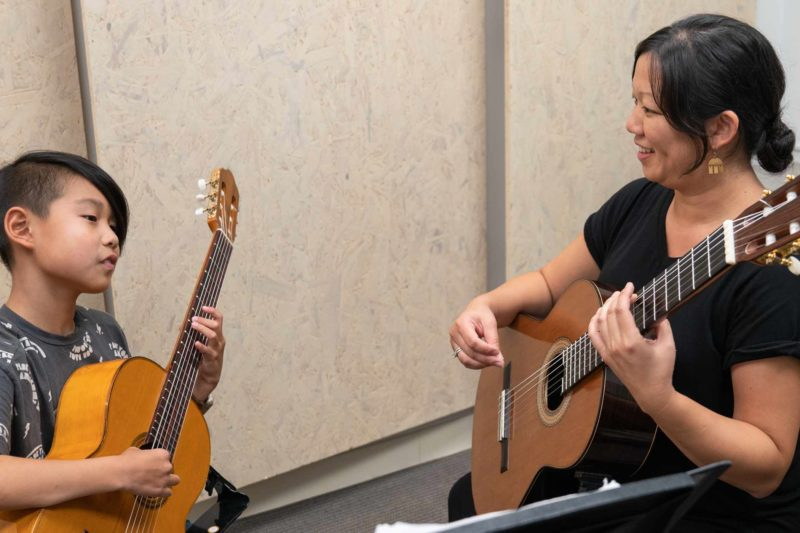 A classical guitar teacher with her young student.