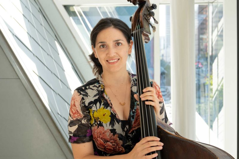 Katie Thiroux wearing a blouse, holding a bass, and smiling in front of a window.