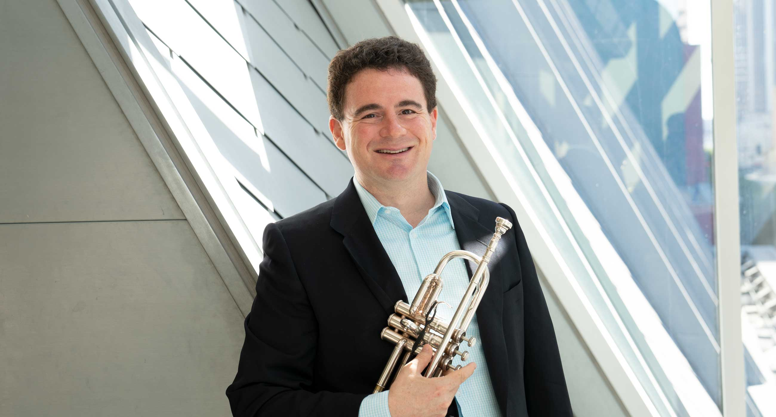 Mike Zonshine wearing a collared shirt and a suit jacket holding a trumpet in front of a window.