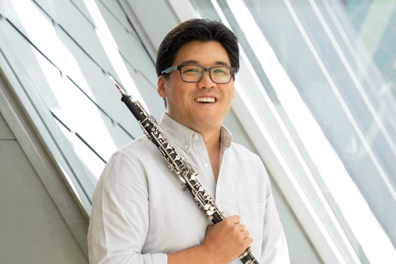 Ted Sugata holding an oboe and smiling in front of a window. He is wearing glasses.