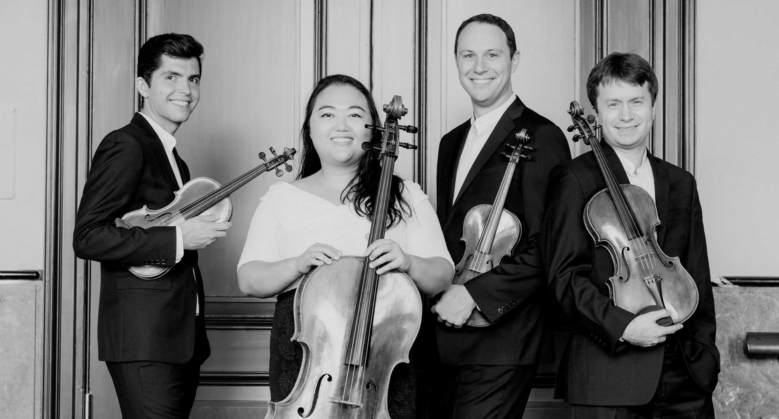The Calidore Quartet holding their instruments and smiling in front of a fancy set of doors.