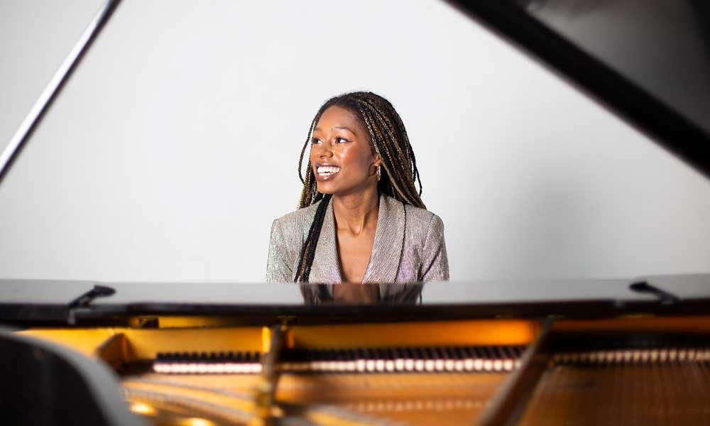 Isata Kanneh-Mason smiling and playing piano.