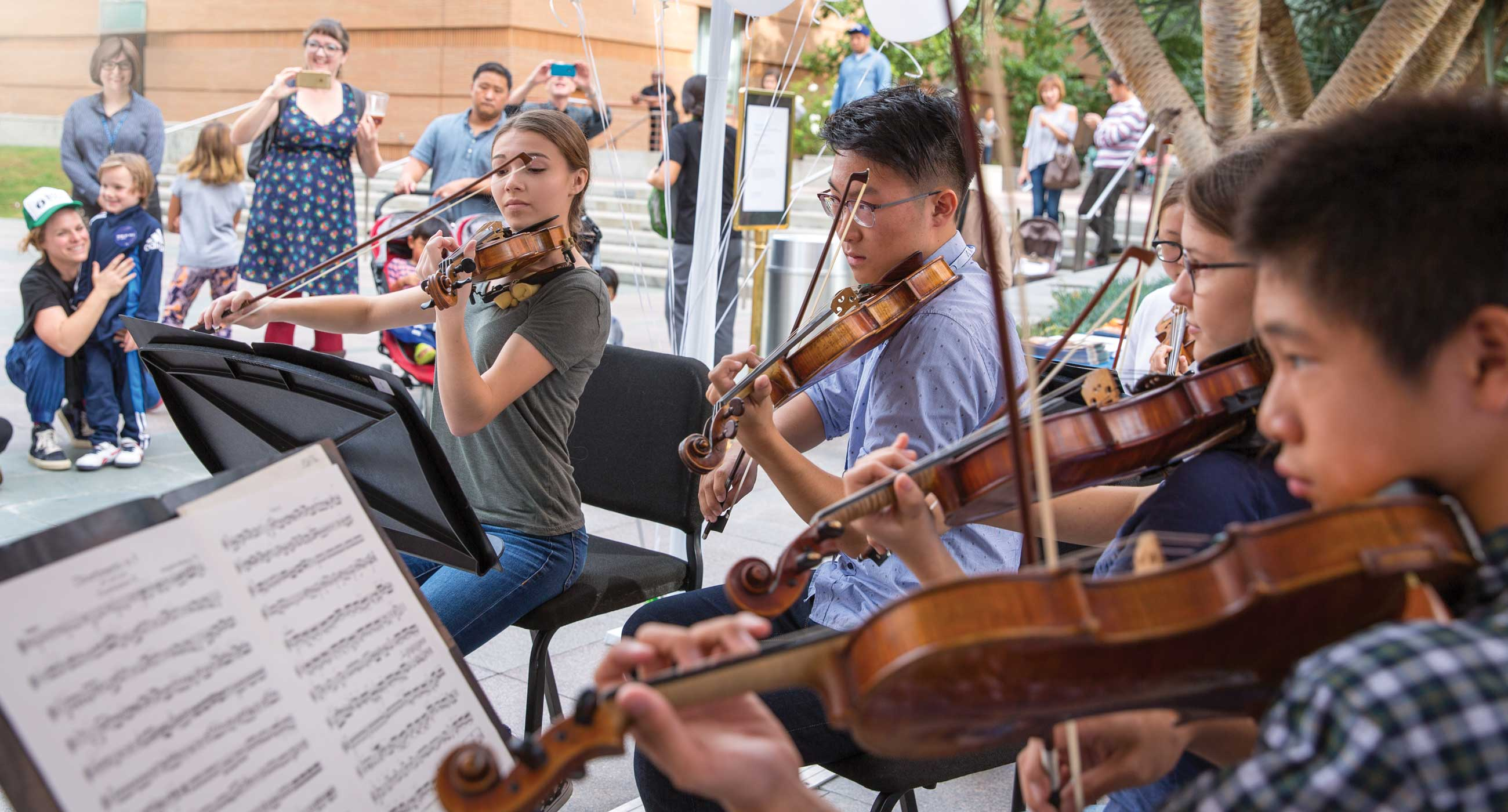 Four students playing violin.