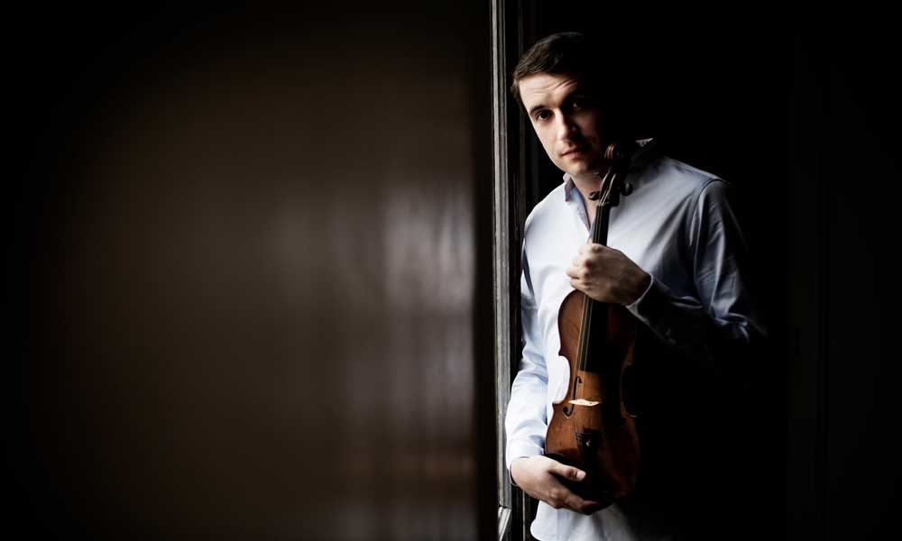 Noah Bendix-Balgley holding a violin and leaning against a wall.