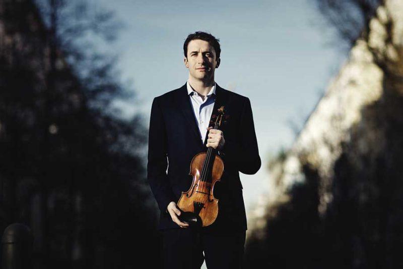 Noah Bendix-Balgley holding a violin.