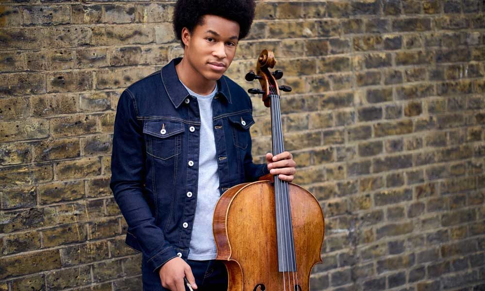 Sheku Kanneh-Mason holding a cello and leaning against a wall.