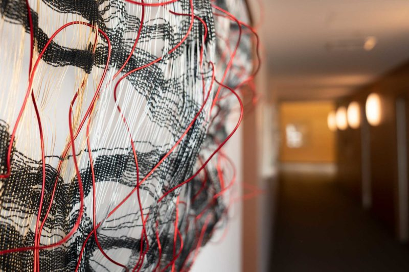 Abstract art hanging on a wall. Two kinds of fibers woven with wire.