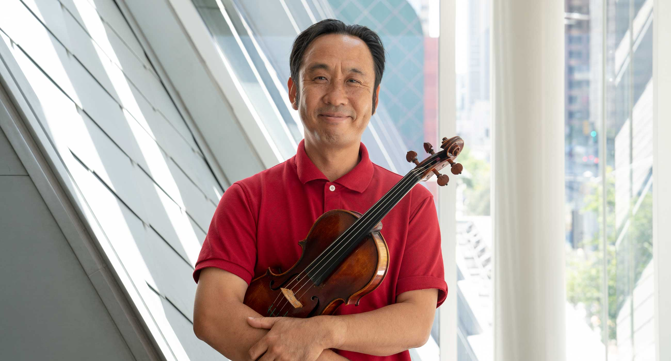 Chan Ho Yun holding a violin and smiling in front of a window.