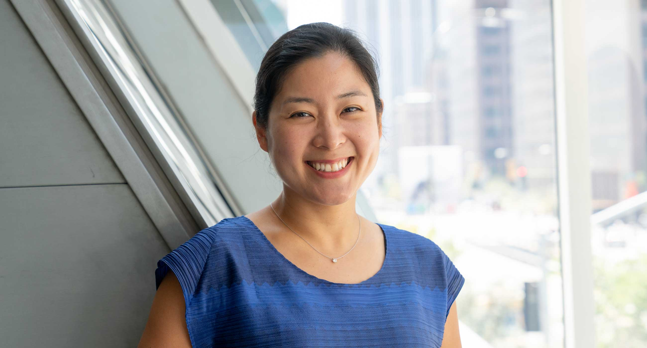 Clara Yang smiling in front of a window.