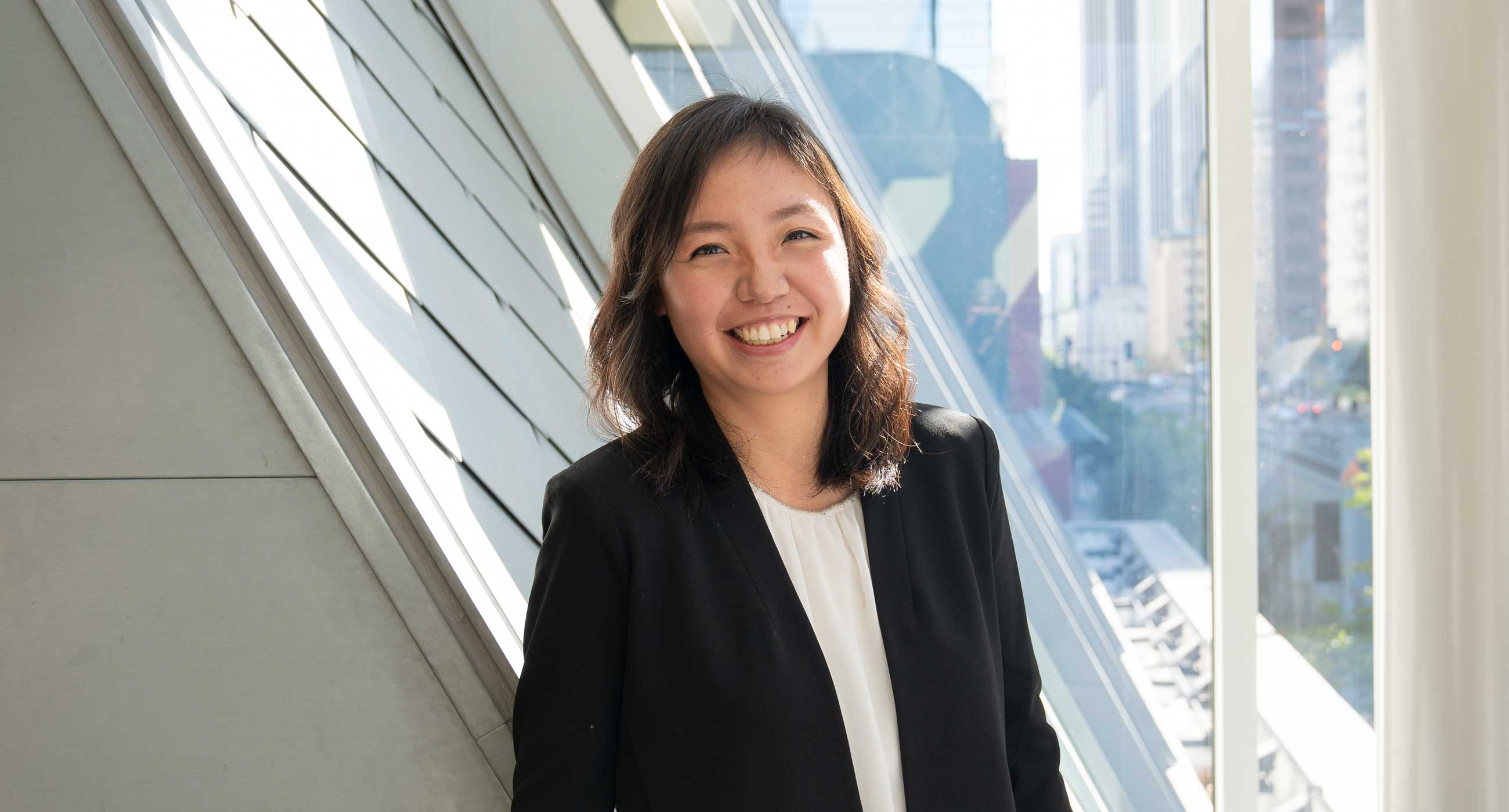 Hui Wu smiling in front of a window, wearing a blazer and a blouse.