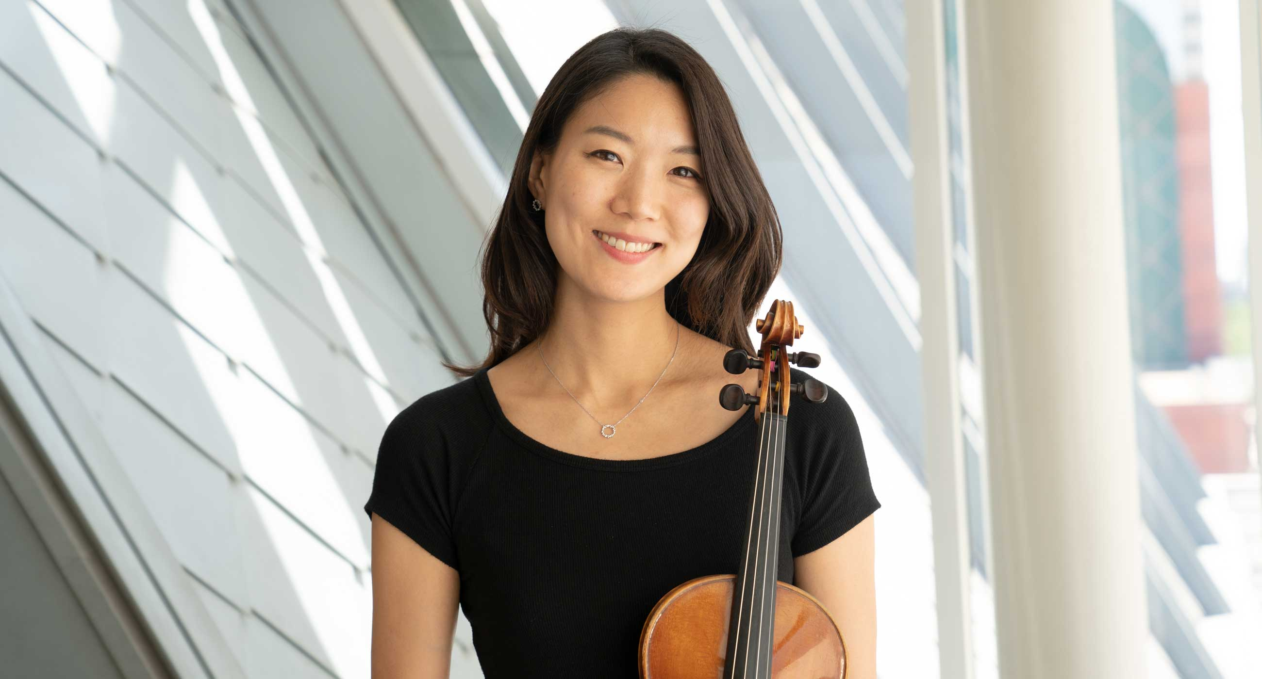 Joanna Lee holding a violin and smiling in front of a window.