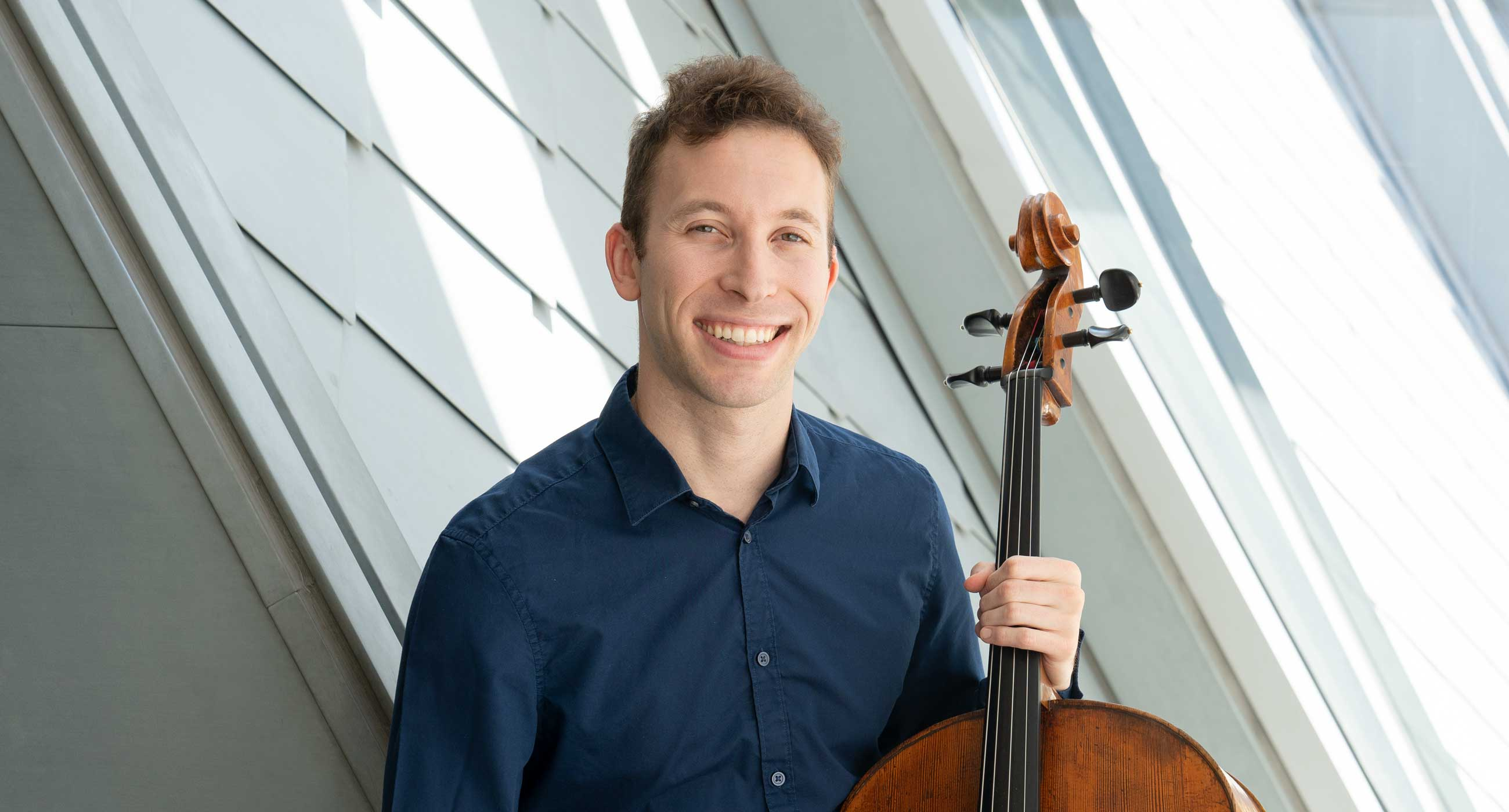 Michael Kaufman wearing a collared shirt, holding a cello, and smiling in front of a window.