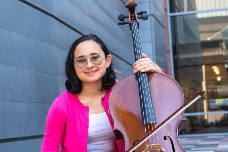 Sarah Kave holding a cello and smiling,