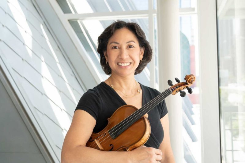 Sherry Cadow holding a viola and smiling in front of a window.