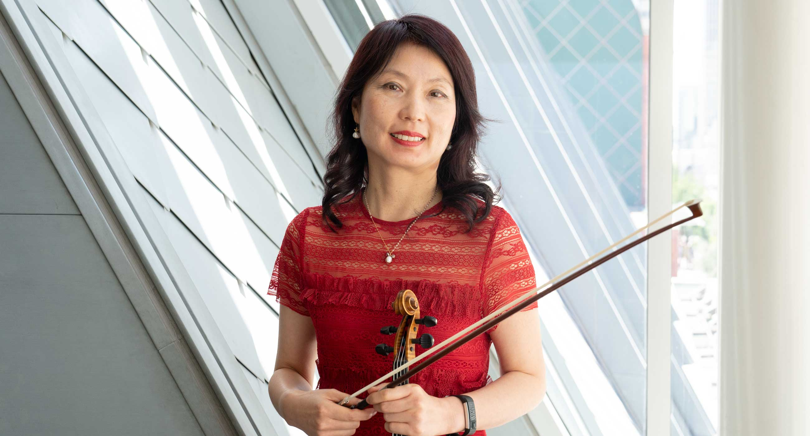 Shih Lan Liu holding a violin and smiling in front of a window.