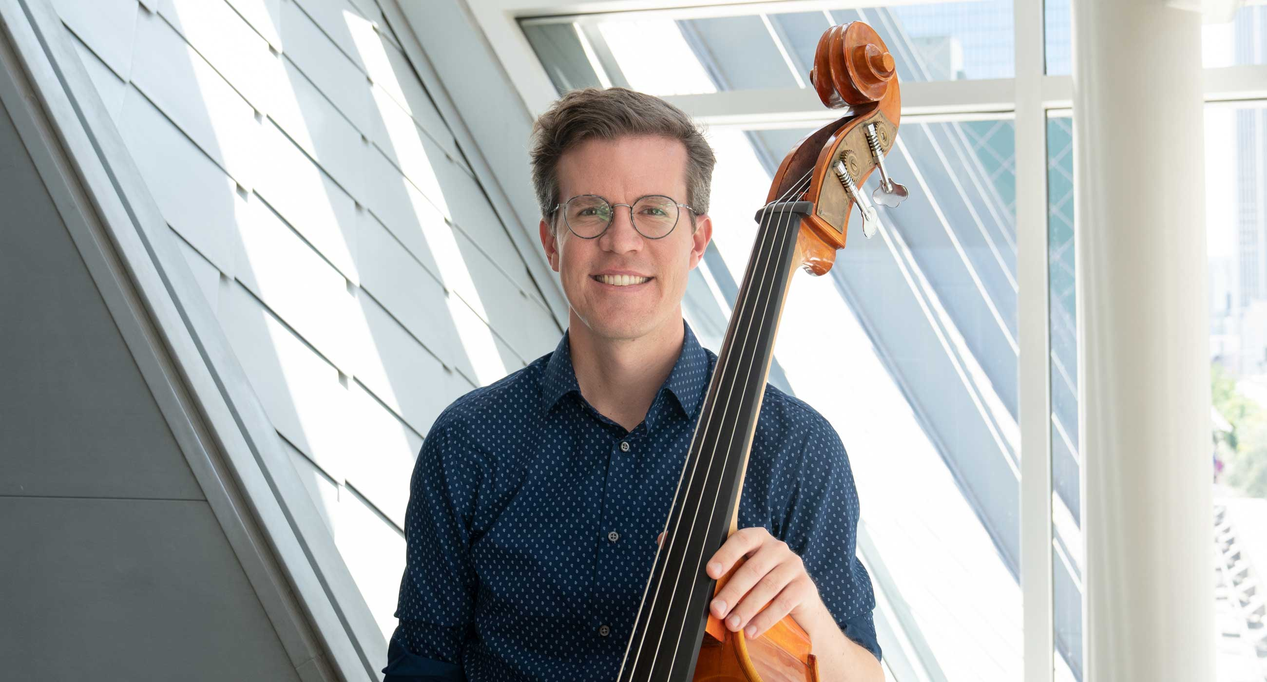 Ted Botsford holding a bass and smiling in front of a window.