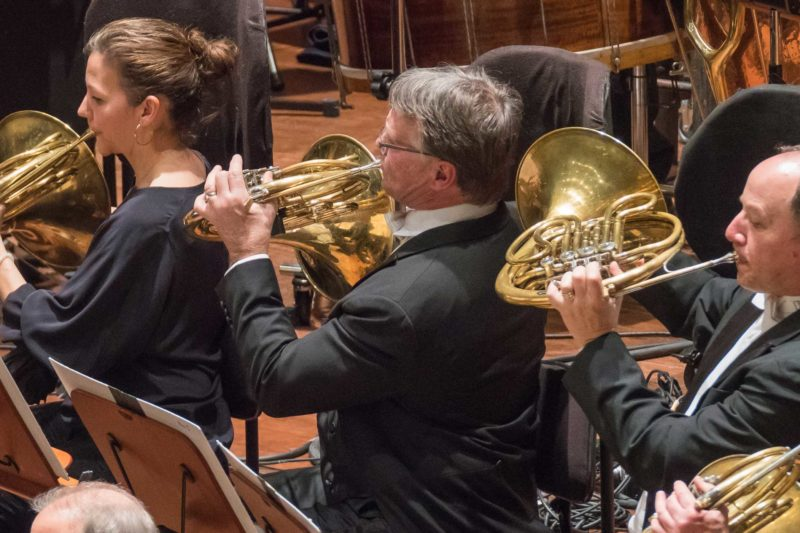 Three horn players, playing horn in an orchestra,