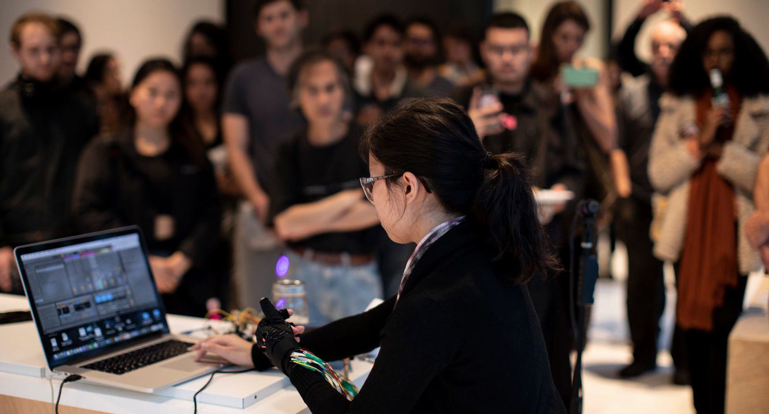 Sara Sithi-Amnuai wearing a custom glove interface sitting in front of a laptop and a crowd of standing people
