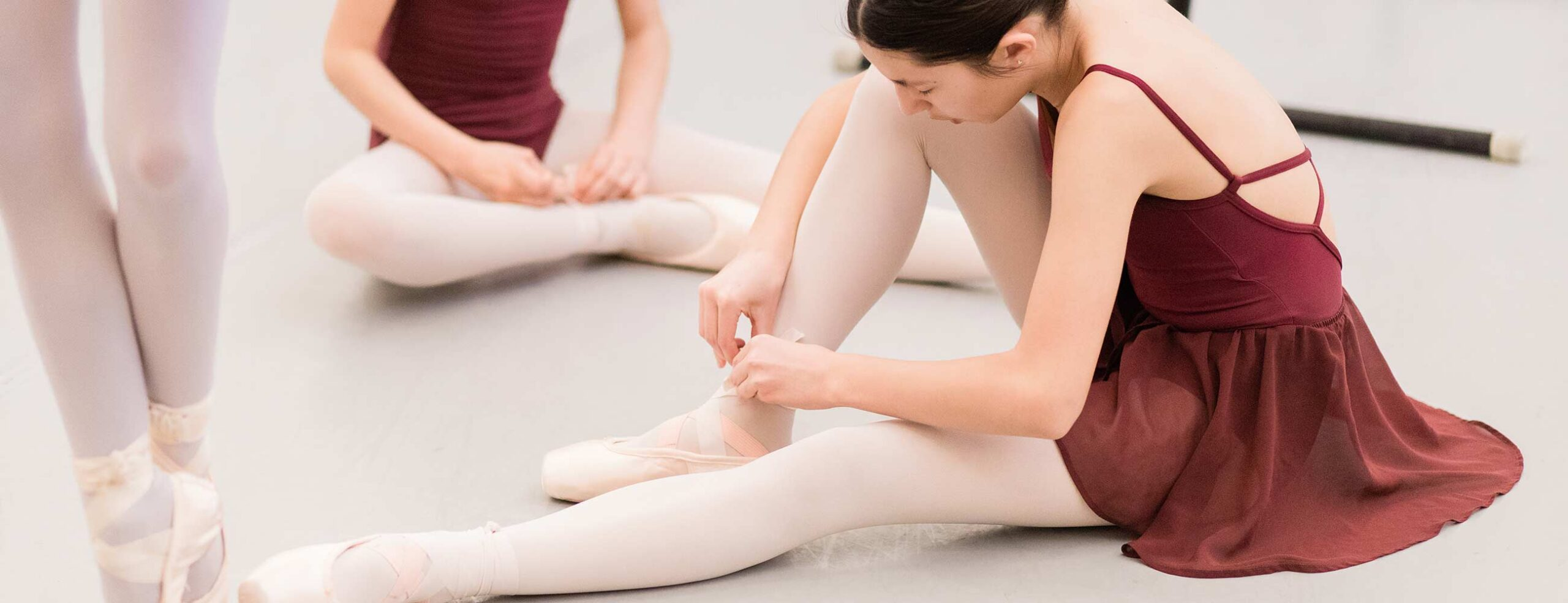 Student on floor tying ballet shoe laces