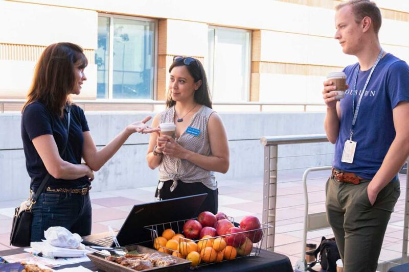 Staff members speaking to a parent on the plaza in front of a table of snacks