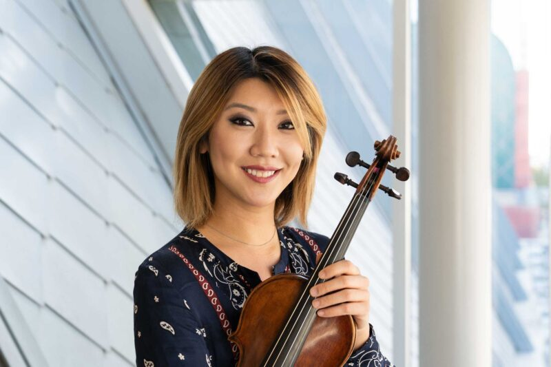 Headshot of Fabiola Kim holding a violin in front of window