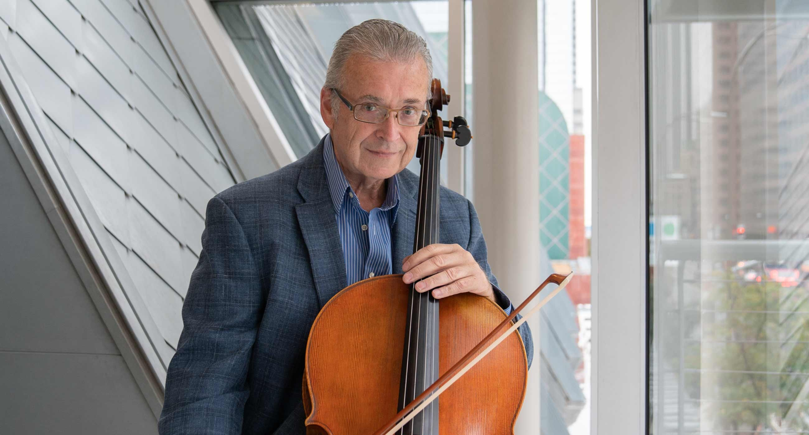 Headshot of John Walz holding a cello in front of window